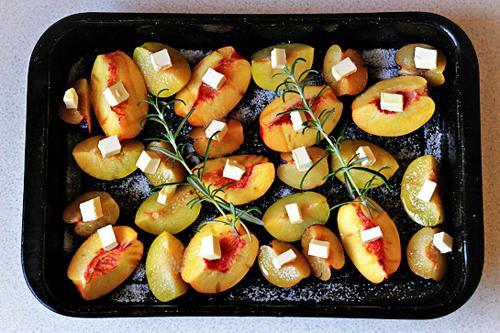 Cắt từng miếng bơ nhỏ, đặt lên trên đầu mỗi miếng hoa quả để chuẩn bị nướng. Cho cây hương thảo vào cho có mùi thơm.