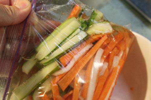 Cho rau củ vào túi ni lon, đổ hỗn hợp giấm đường vào bóp nhẹ.