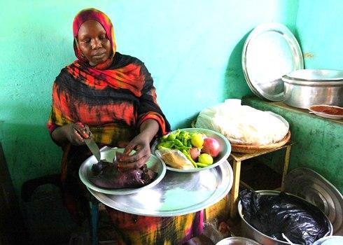 Một phụ nữ ở Al Jazeera, Sudan chuẩn bị một món ăn với gan lạc đà. Từ năm 1996 đến năm 2002, Sudan ước tính đã sản xuất giữa 72.000 và 81.000 tấn thịt lạc đà mỗi năm.